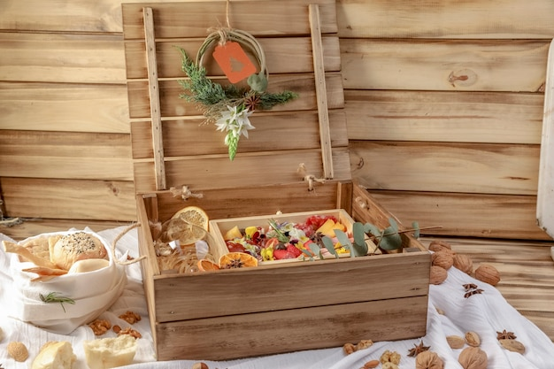 Coffret cadeau de noël en bois, avec des ustensiles traditionnels italiens: vin rouge et prosciutto cru, salami, parmesan, olives et pain.