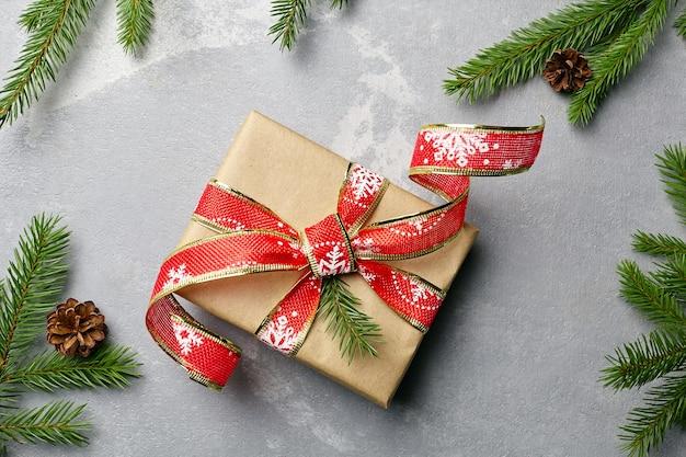 Coffret cadeau de noël avec décoration de ruban rouge festif et branches de sapin sur fond gris, vue de dessus