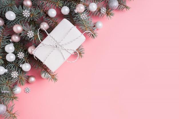 Coffret cadeau de noël avec décorations en argent, boules de verre et branches de sapin sur rose.