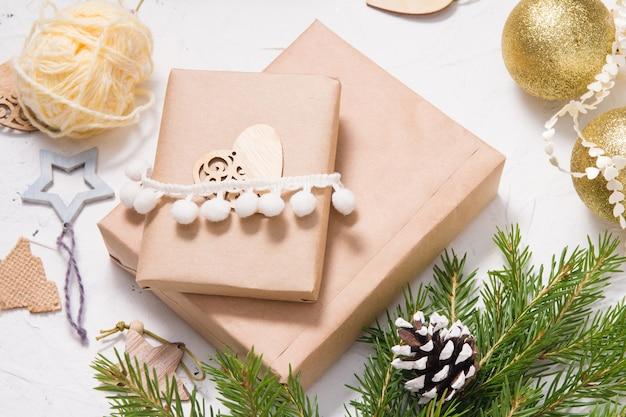 Coffret cadeau de noël emballé dans du papier kraft et décoré d'un coeur en bois et de branches de sapin, matériaux naturels pour la décoration de cadeaux sur fond blanc, concept de noël écologique
