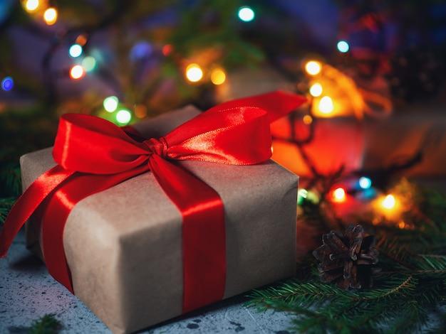 Coffret cadeau de noël emballé dans du papier kraft et ruban rouge sur table avec des branches d'arbres de noël et guirlande