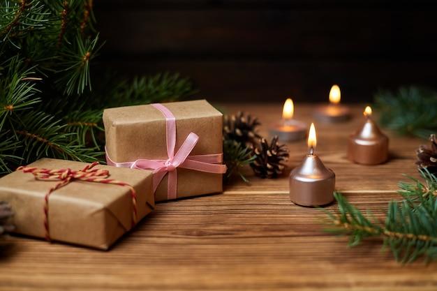 Coffret cadeau de noël sur fond de bougies allumées, de branches de sapin et de cônes