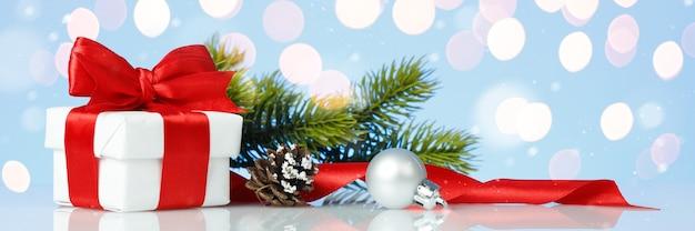 Coffret cadeau de noël avec noeud rouge et décorations avec lumières dorées