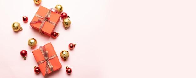 Coffret cadeau de noël avec ruban de satin, boules dorées et rouges sur fond rose.
