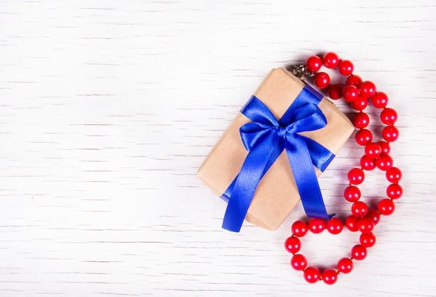 Coffret cadeau avec noeud bleu et perles de corail rouges sur fond de bois blanc