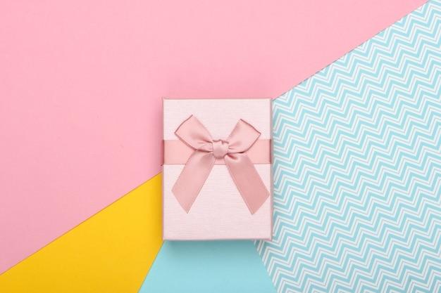 Coffret cadeau avec noeud sur fond coloré. tendance couleur pastel. vue de dessus