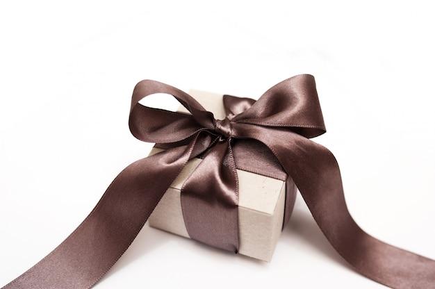 Coffret cadeau avec un noeud marron sur un blanc