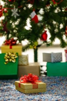 Coffret cadeau avec noeud rouge placé sur un tapis près des jouets le jour de noël à la maison