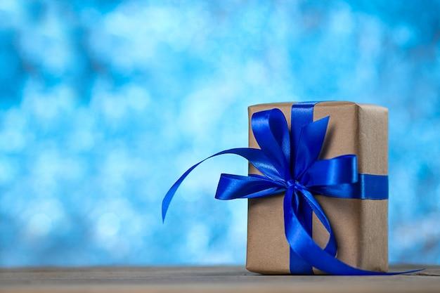 Coffret cadeau avec un noeud de ruban sur le bureau sur bleu