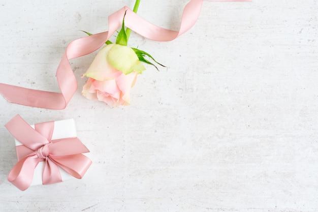 Coffret cadeau avec un noeud en satin rose et rose sur fond de bois blanc