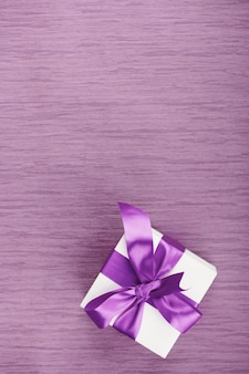 Un coffret cadeau avec noeud violet sur fond rose. vertical avec espace copie