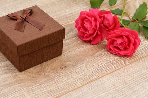Coffret cadeau noyer avec des roses rouges sur le fond en bois. concept de donner un cadeau en vacances. vue de dessus.
