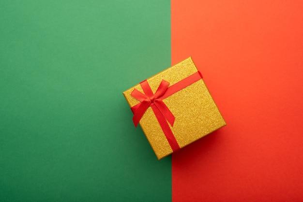 Coffret cadeau en or avec ruban rouge sur fond vert et rouge vif vue de dessus à plat