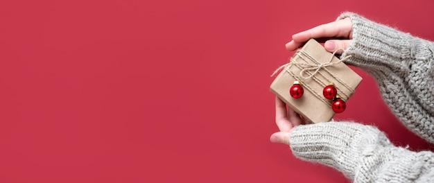 Coffret cadeau en papier kraft dans les mains des femmes sur fond rouge. bannière panoramique lumineuse, nouvel an, espace de copie. offrir des cadeaux pour noël, vente, remises.