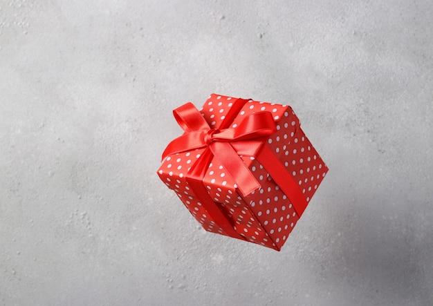 Coffret cadeau en papier rouge avec un ruban rouge vole sur une surface gris clair