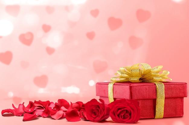 Coffret cadeau et pétales de rose rouges sur fond rose