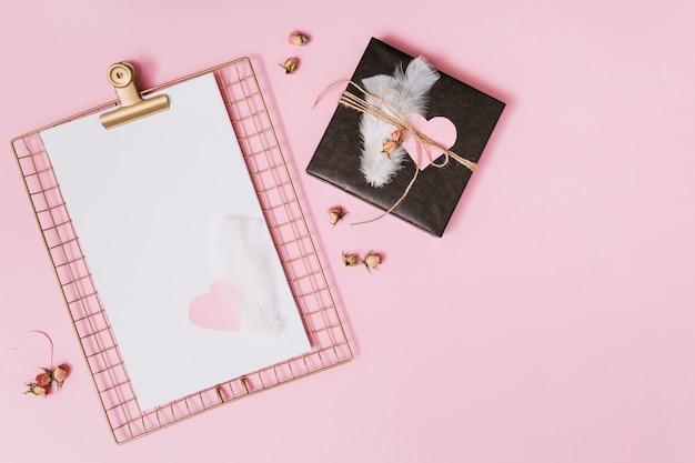Coffret cadeau avec plumes et coeur d'ornement près du presse-papiers avec papier