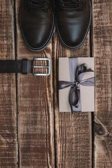Coffret cadeau pour la fête des pères avec ceinture d'accessoires pour hommes et chaussures en cuir sur une table en bois. mise à plat.
