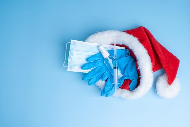 Coffret cadeau pour les fêtes de fin d'année 2021. un ensemble hygiénique d'un masque médical, de gants, d'un désinfectant et d'une seringue avec un vaccin et une puce de coronavirus dans un chapeau de père noël. vaccination 2021.