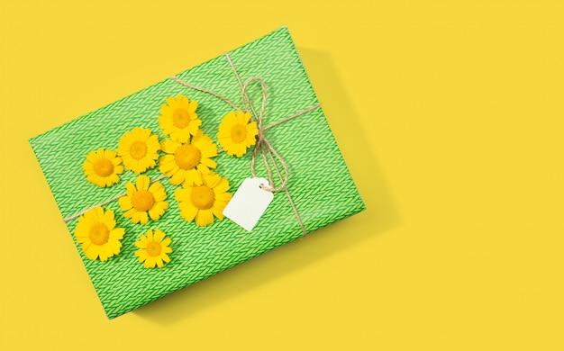 Coffret cadeau ou présent avec étiquette vierge et fleurs de marguerite sur fond jaune. copiez l'espace vue de dessus.