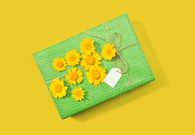Coffret cadeau ou présent avec étiquette vierge et fleurs de marguerite sur fond jaune. vue de dessus.