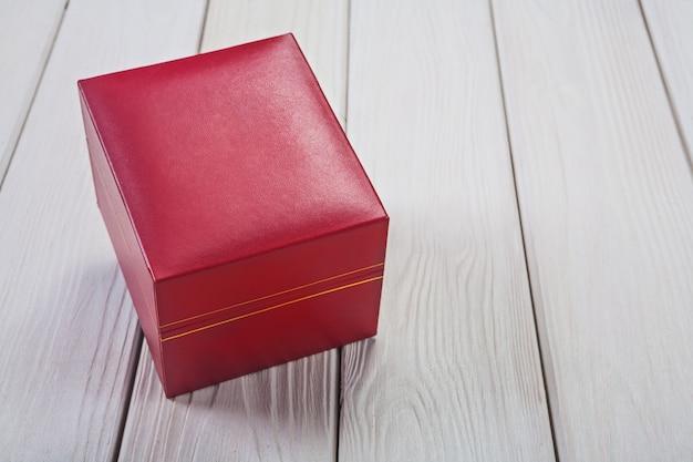 Coffret cadeau recouvert de cuir texturé doux rouge sur des planches en bois blanc