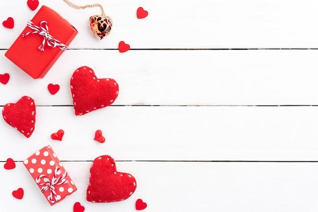 Coffret cadeau rouge, fond rouge saint valentin avec coeur rouge sur fond en bois.