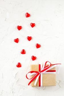 Coffret cadeau avec ruban arc rouge et blanc et coeurs sur table blanche pour la saint valentin. vue de dessus avec espace copie