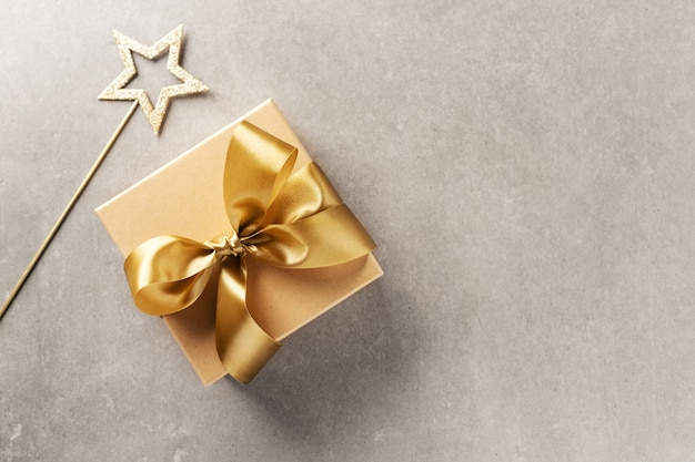 Coffret cadeau avec ruban doré sur gris