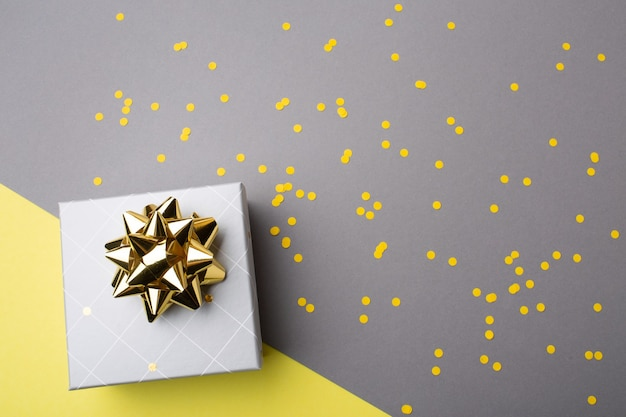 Coffret cadeau avec ruban jaune et confettis sur fond de papier gris ultime. couleurs de l'année 2021. vue de dessus