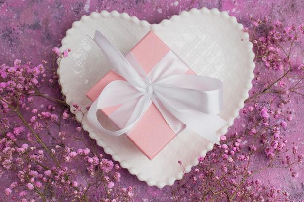 Un coffret cadeau avec un ruban rose sur une assiette en forme de soucoupe blanche et un gypsophile.