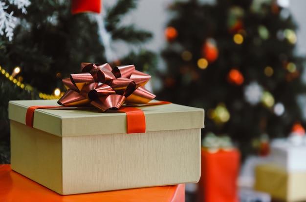 Coffret cadeau avec ruban rouge sur le bureau avec arbre de noël et lumières bokeh, cadeau de nouvel an
