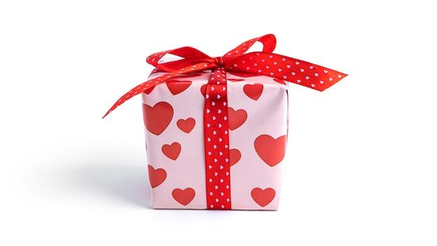 Coffret cadeau avec ruban rouge et coeurs isolés sur surface blanche