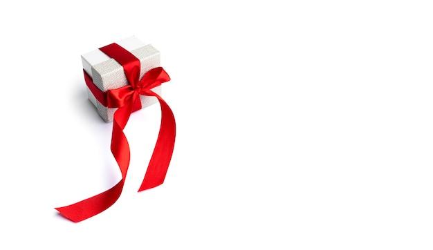 Coffret cadeau avec ruban rouge isolé sur surface blanche