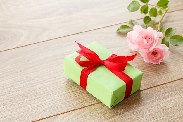 Coffret cadeau avec ruban rouge sur des planches en bois décorées de fleurs roses roses. vue de dessus.