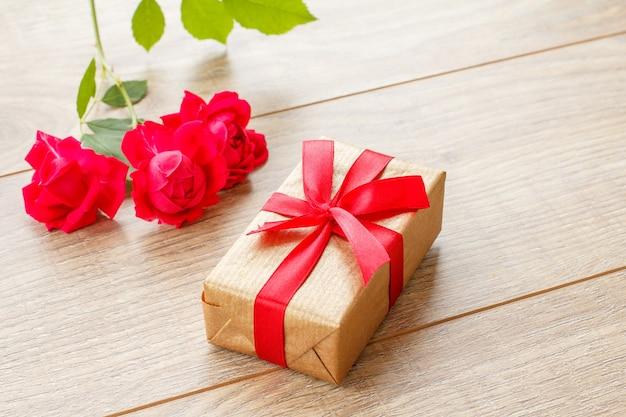 Coffret cadeau avec ruban rouge sur des planches en bois décorées de fleurs roses rouges. vue de dessus.