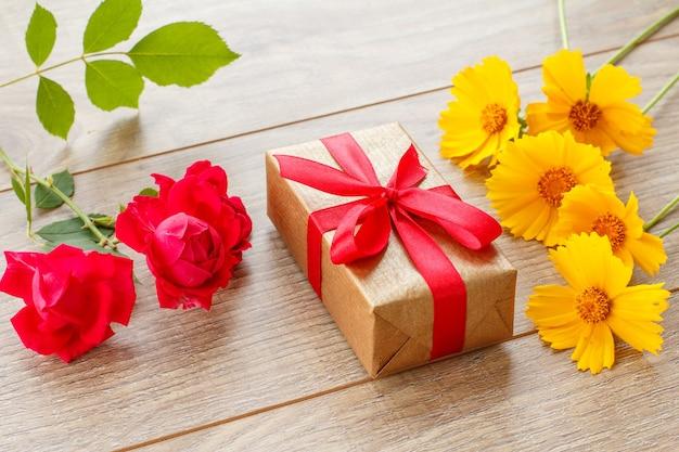 Coffret cadeau avec ruban rouge sur des planches en bois décorées de roses rouges et de fleurs jaunes. vue de dessus.