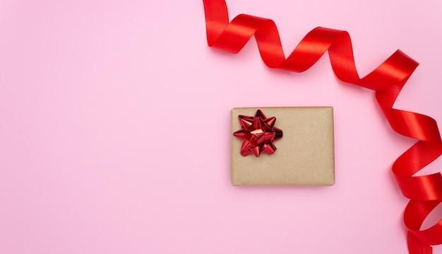 Coffret cadeau et ruban de satin rouge sur le côté sur fond rose