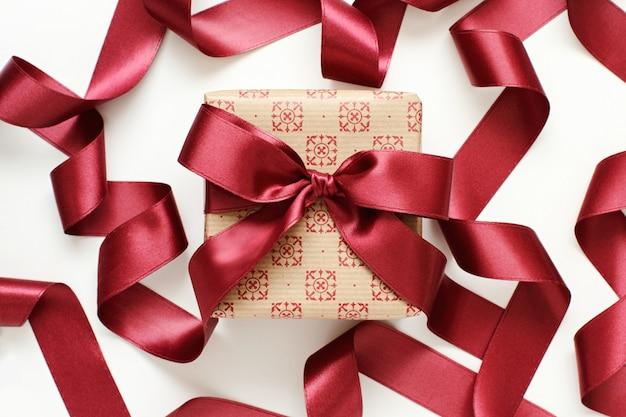Coffret cadeau avec ruban de satin rouge foncé isolat
