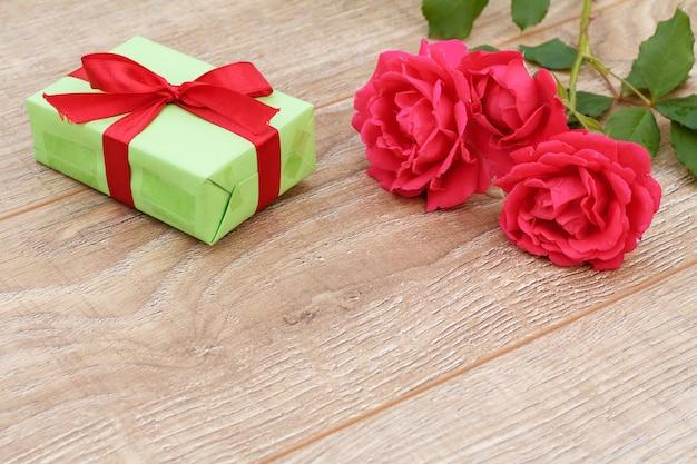 Coffret cadeau avec des rubans rouges et de belles roses rouges sur le fond en bois. concept de donner un cadeau en vacances. vue de dessus.