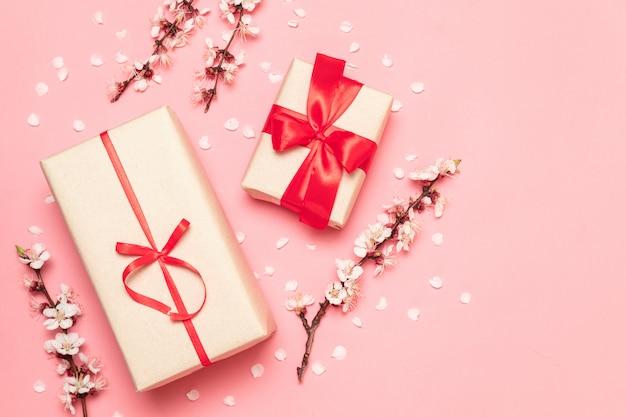 Coffret cadeau avec des rubans rouges avec un brin de fleurs sur fond rose avec un espace pour le texte