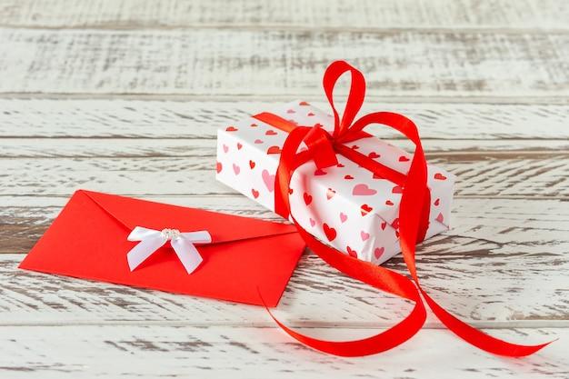 Coffret cadeau saint valentin avec enveloppe avec lettre d'amour, coeurs en papier sur fond en bois. carte de voeux pour la saint valentin ou l'anniversaire.