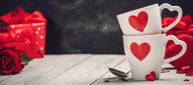Coffret cadeau saint valentin tasses et roses sur un fond en bois