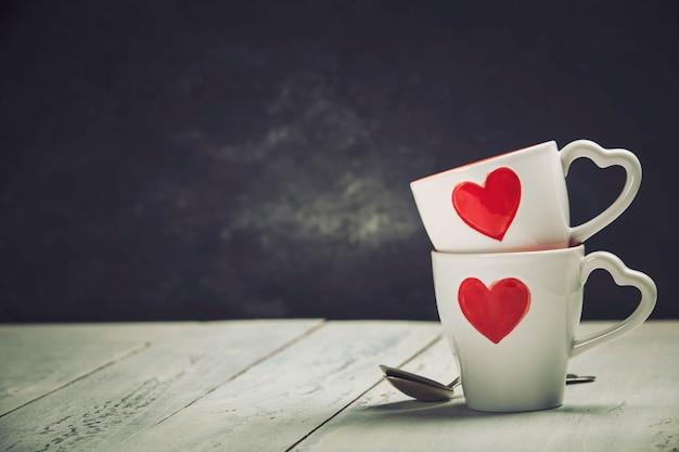 Coffret cadeau saint valentin tasses rouges sur fond de bois.