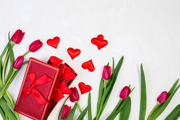 Coffret cadeau avec saint valentin et tulipes rouges sur fond blanc texturé avec espace copie