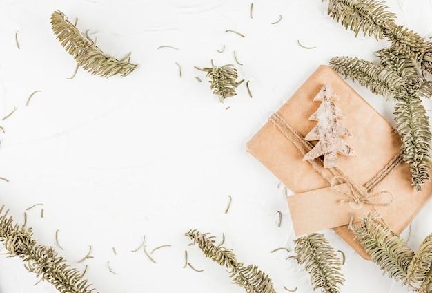 Coffret cadeau avec sapin décoratif et étiquette près de branches de conifères