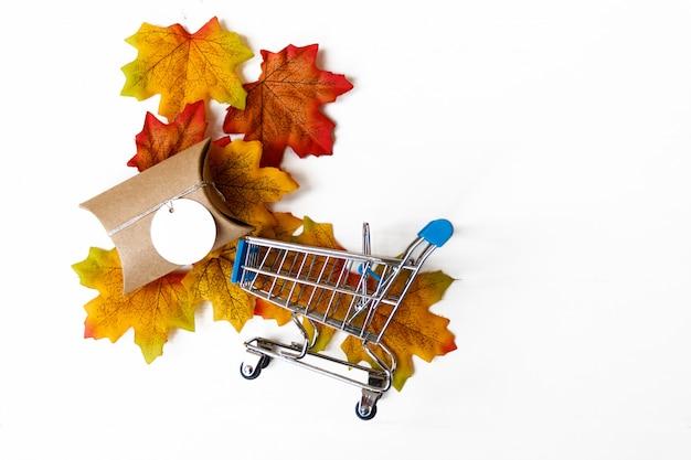 Le coffret cadeau et shopping sur feuille d'érable et fond