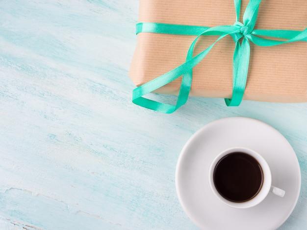 Coffret-cadeau surprise de vacances d'anniversaire emballé avec ruban vert et tasse de café expresso
