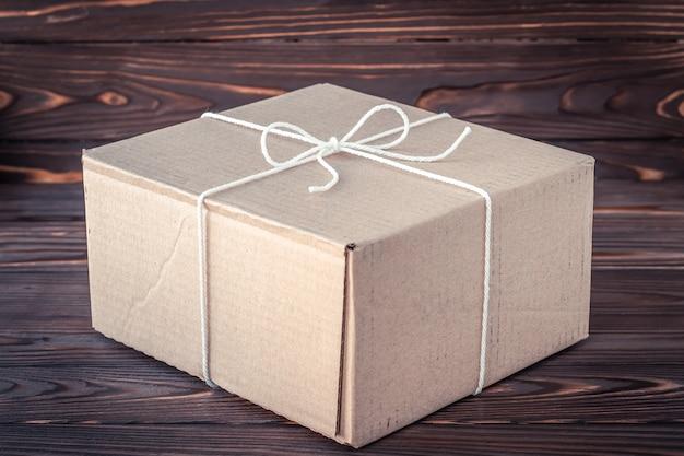 Coffret cadeau sur table en bois marron. concept de service de livraison de colis. boîte en carton avec noeud de corde.