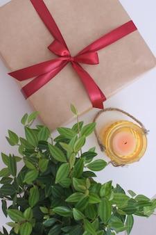 Coffret cadeau sur la table avec une feuille verte et une bougie birhday noël nouvel an